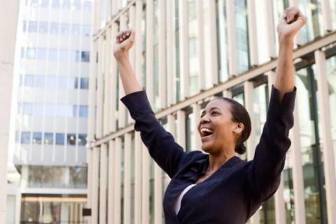 Woman in suit throws hands in air in glee