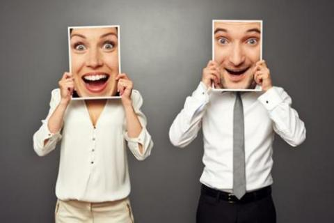 Workers hold up funny faces to create office humour