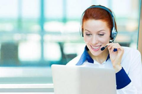 Woman on telephone headset in front of computer