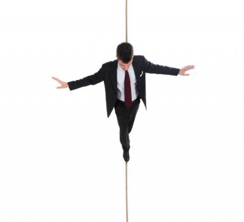 Professional walking on a tightrope trying to achieve work-life balance