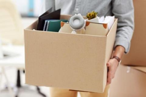 Employee carries box full of desk items after being fired from their creative job