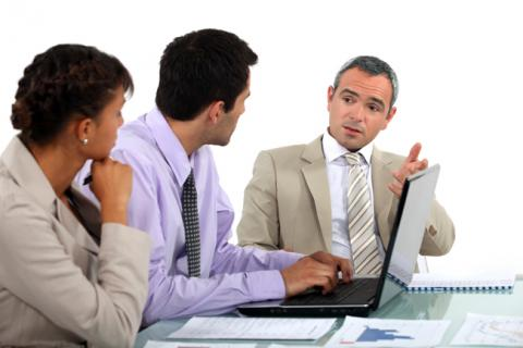 Three financial professionals share ideas during a meeting