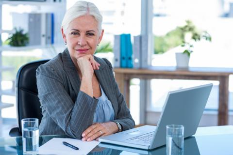 Baby Boomer sits at her desk and considers consulting instead of retiring
