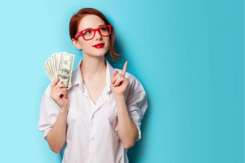 Young woman with red glasses holding money.