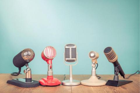 Five microphones lined up on a table.