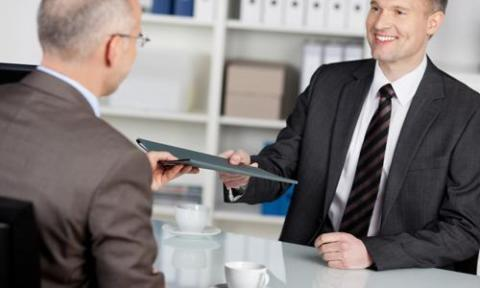 Man having second interview hands resume to interviewer