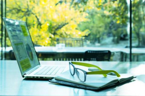 Eyeglasses and laptop on a desk to illustrate telecommuter programs
