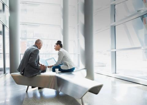 Two business people sitting on a bench having a meeting.