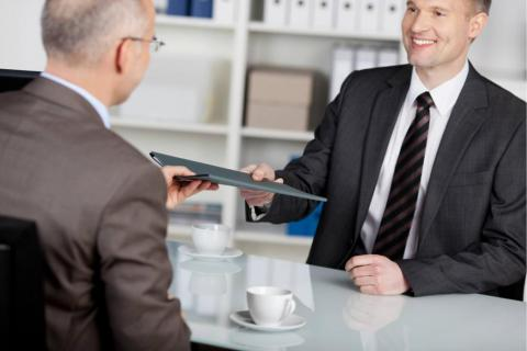 man at table handing folder to another man