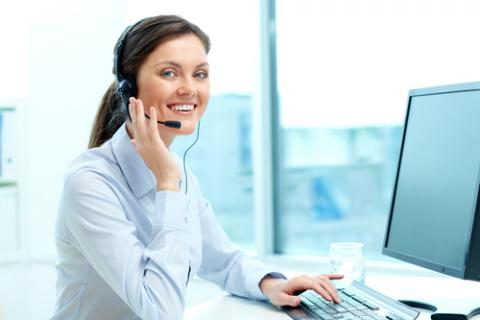 receptionist smiling at a computer
