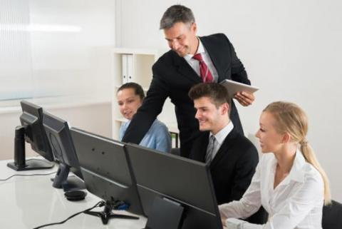 3 professionals at computers receiving direction from boss