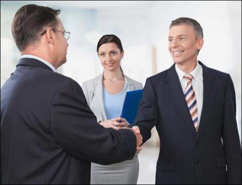 Two business men shake hands and business woman watches