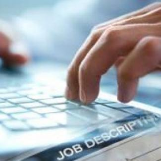 Hands typing on a computer, creating a compelling IT job posting