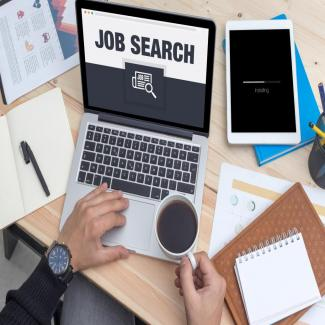 Hand at laptop with the words job search and tools to find the best accounting jobs