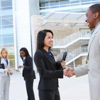 Man and woman shaking hands outside an office building at end of hiring process