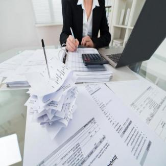 Bookkeeper or accountant at paper-laden desk offering temporary help