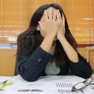 Woman covering her face after making mistakes at work