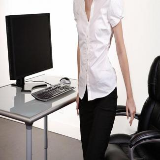A woman in business attire is walking through an office.