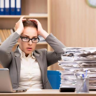 Employer looks at pile of paper and needs to hire a seasonal employeee