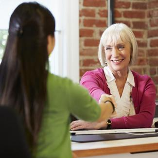 A hiring manager shakes the hand of a candidate during an interview