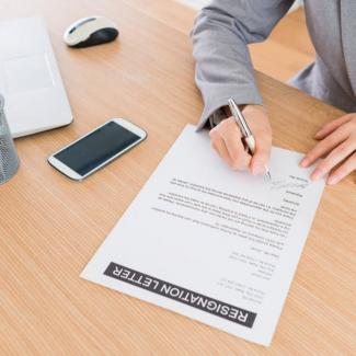 How to Write a Resignation Letter — Person signing resignation letter at desk with computer and phone