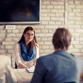 8 Common Job Interview Questions and Answers — job candidate at table with three interviewers