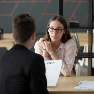 What Is a Staffing Agency? — Man holding resume talking to woman at office table