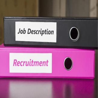 "Photo of a black binder reading ""Job Description"" on top of a pink binder reading ""Recruitment"""