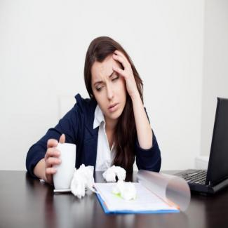 What to Do When Calling in Sick is Unavoidable — woman at a desk holding a tissue with one hand on her head