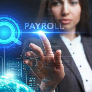 "What You Should Know About the Latest in Payroll Technology — Woman pointing to word ""payroll"" on glass"